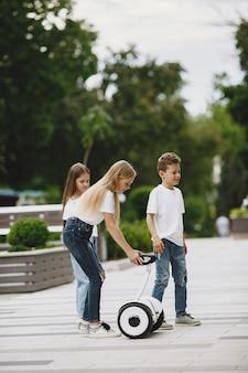 Kinderen leren hoverboard rijden in een park op zonnige zomerdag