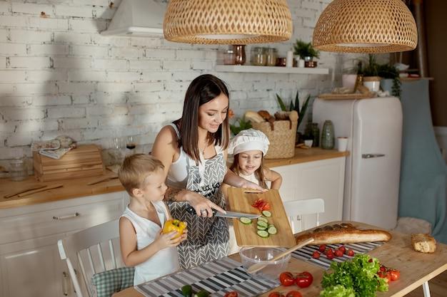 Kinderen leren in de keuken een salade bereiden. familiedag, lunch met je eigen handen. moeder en jonge koks