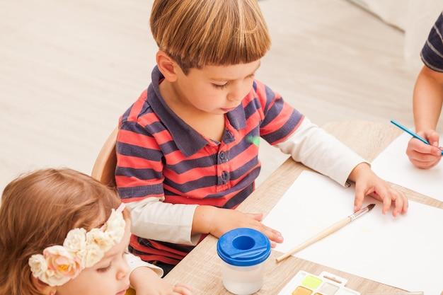 Kinderen leren schilderen met een penseel en aquarellen op papier in de kleuterschool