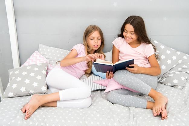 Kinderen lezen boek in bed. familie traditie. meisjes beste vrienden lezen sprookje voor het slapengaan. beste boeken voor kinderen. lezen voor het slapengaan kan helpen om 's nachts beter te slapen. verhalen die elk kind zou moeten lezen.