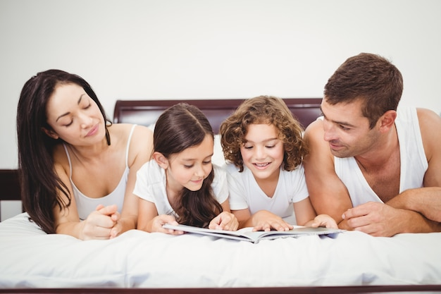 Kinderen lezen boek met ouders thuis