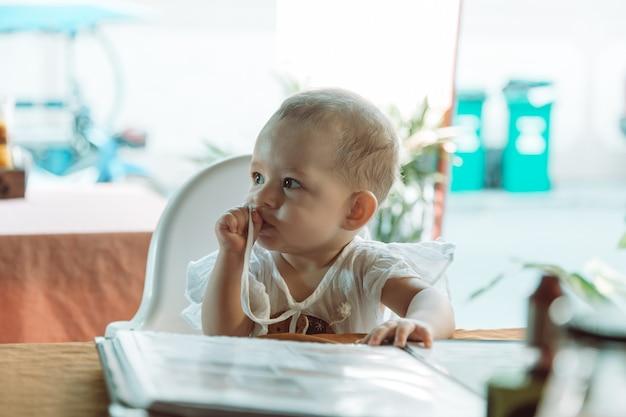 Kinderen lezen menu in restaurant babymeisje zit op een kinderstoel in straatcafé