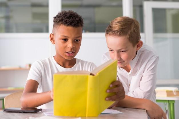 Kinderen lezen samen uit een boek