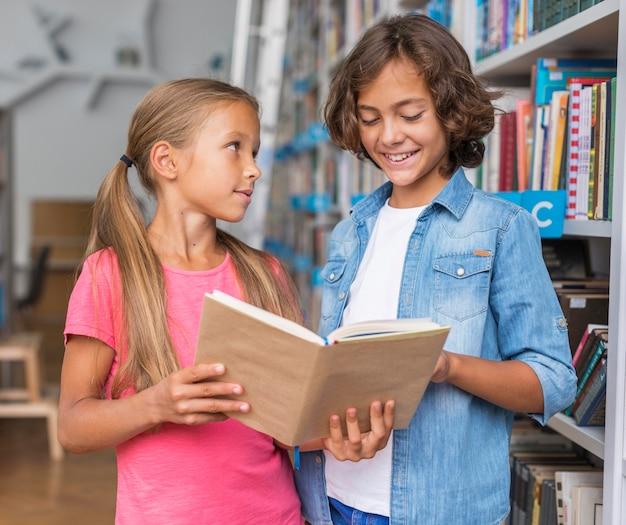 Kinderen lezen uit een boek in de bibliotheek