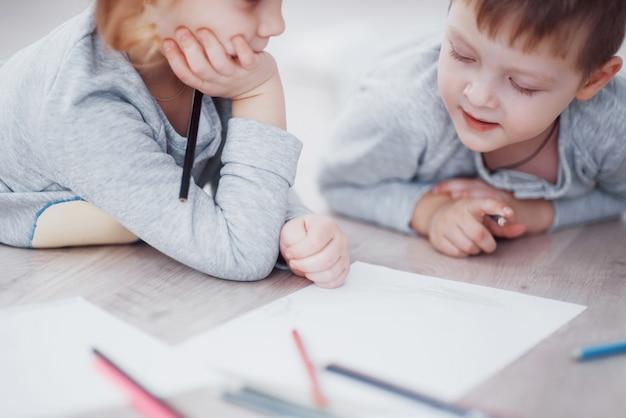 Kinderen liggen op de vloer in pyjama en tekenen met potloden. het leuke kind schilderen door potloden. de hand van kindmeisje en de jongen trekken en schilderen met kleurpotlood. close-up weergave