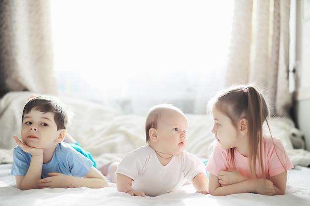 Kinderen liggen op het bed naast de pasgeboren baby, zusje. emoties van kinderen.