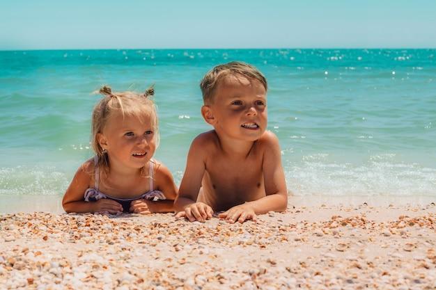 Kinderen liggen op het strand van de zee