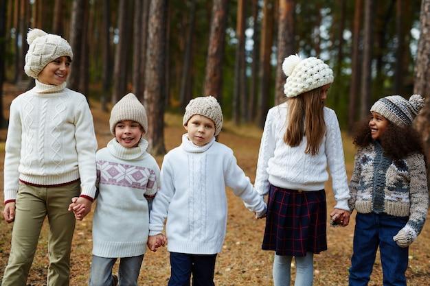 Kinderen lopen het bos in