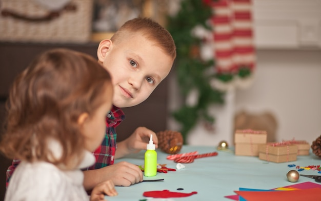 Kinderen maken decor voor kerstboom of cadeaus. handgemaakt diy-project voor kerstmis.