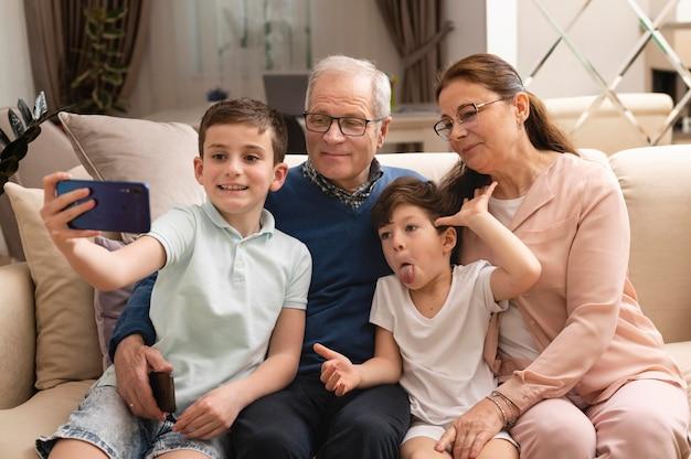 Kinderen maken een selfie met hun grootouders op de bank