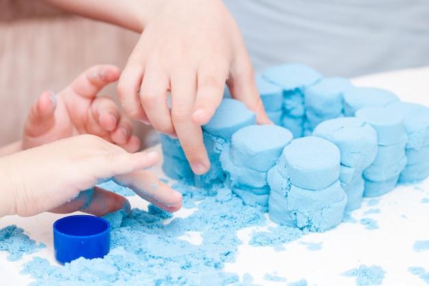 Kinderen maken figuren van blauw kinetisch zand