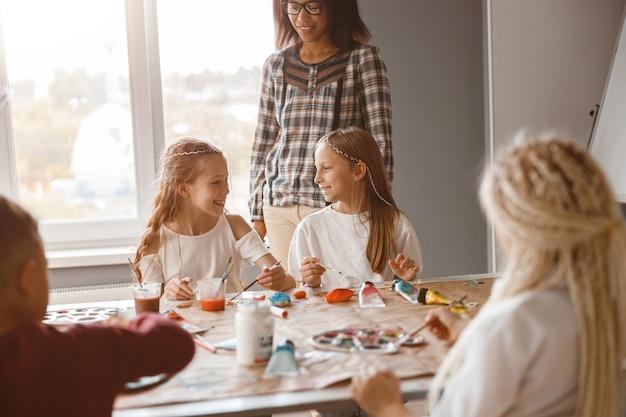 Kinderen maken kunstschilderijen met aquarelverf