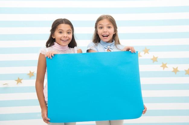 Kinderen maken reclame. reclame voor uw product. lachende kleine meisjes kinderen houden blauwe advertentieposter voor kopieerruimte. kleine meisjes met blauw papier.