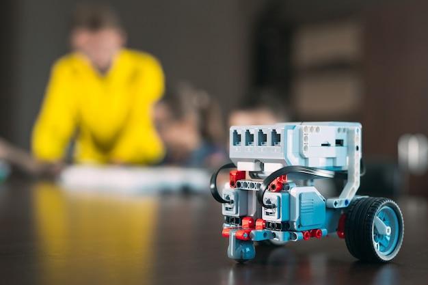 Kinderen maken robots met leraar. vroege ontwikkeling, diy, innovatie, moderne technologie.