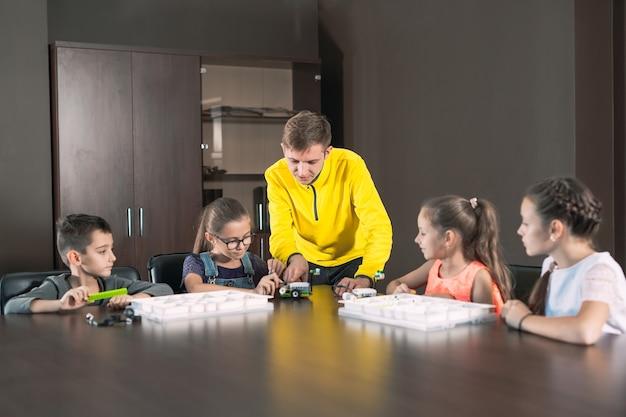 Kinderen maken robots met leraar.
