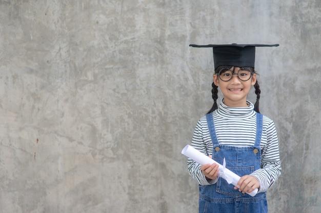 Kinderen meisje draagt een gediplomeerde pet op witte achtergrond erg blij en opgewonden