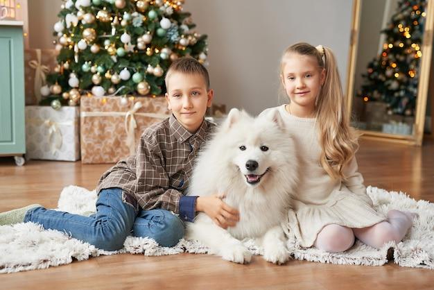 Kinderen meisje en jongen met samojeed hond op scène van kerstmis