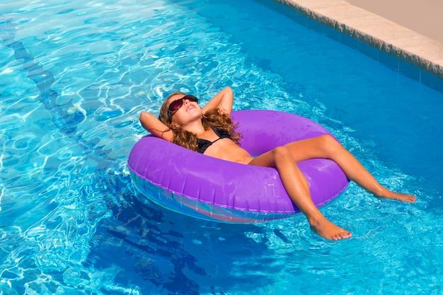 Kinderen meisje ontspannen op paars opblaasbaar zwembad ring