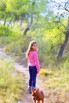 Kinderen meisje wandelen in het dennenbos met hond