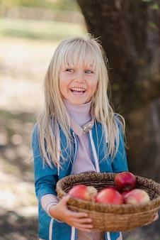 Kinderen met appel in boomgaard. oogstconcept.