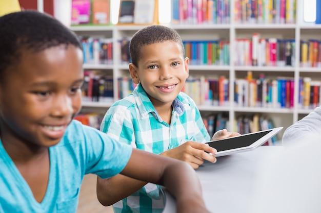 Kinderen met behulp van digitale tablet in de bibliotheek