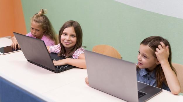 Kinderen met behulp van laptop op school