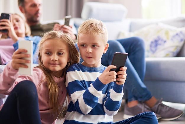 Kinderen met behulp van mobiele telefoon in de woonkamer