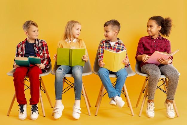 Kinderen met boeken kijken naar elkaar