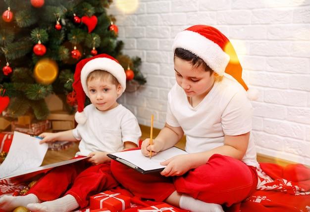 Kinderen met brief aan de kerstman thuis tijdens kerst gelukkig nieuwjaar
