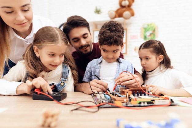 Kinderen met de leraar werken met een soldeerbout.