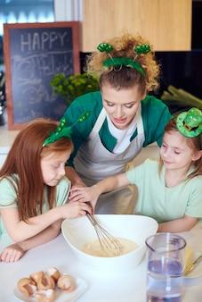 Kinderen met draadklopper bakken cupcakes in de keuken