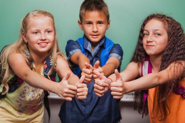 Kinderen met duimen omhoog op schoolbord