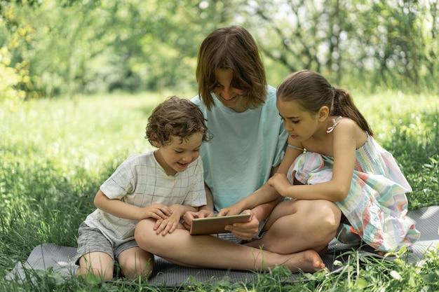 Kinderen met een tablet buitenshuis kinderen spelen spelletjes op het tablettechnologieconcept