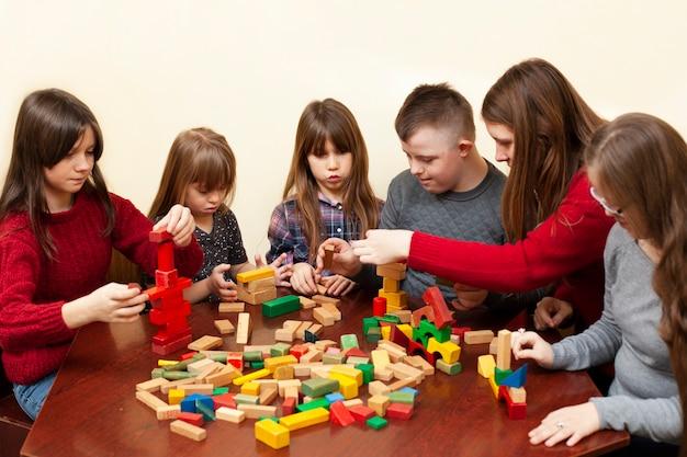 Kinderen met het syndroom van down spelen met vrouw en speelgoed