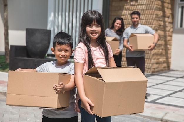Kinderen met kartonnen doos staan voor het huis