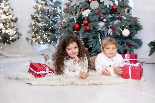 Kinderen met kerstcadeautjes in hun handen in de buurt van de kerstboom en lampjes