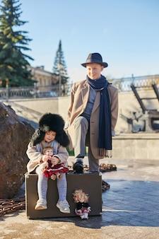 Kinderen met koffers reizen, retro herfst lente kleding. een klein kind zit op een koffer en wacht op de treinbus