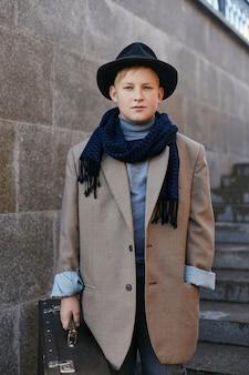 Kinderen met koffers reizen, retro herfst lente kleding. een klein kind zittend op een koffer