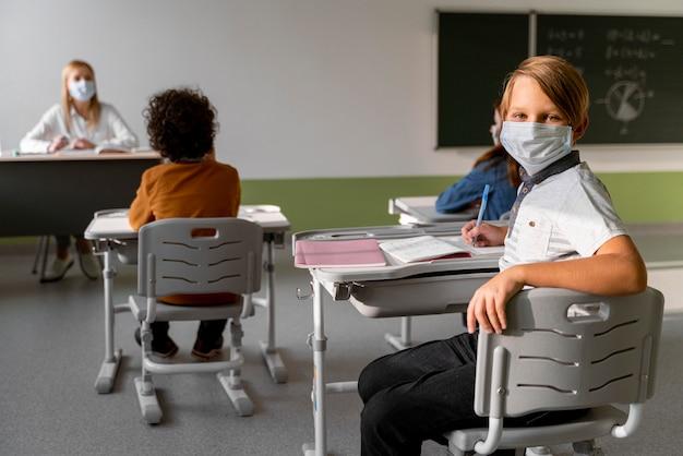 Kinderen met medische maskers leren op school met vrouwelijke leraar