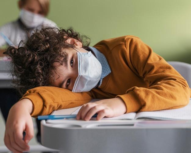 Kinderen met medische maskers vervelen zich in de klas op school
