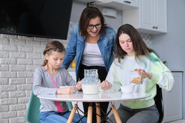Kinderen met moeder die thuis in keuken eten