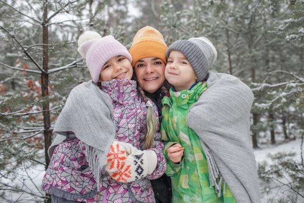 Kinderen met moeder genieten van eerste sneeuw in winterbos, actieve seizoensactiviteiten, levensstijl