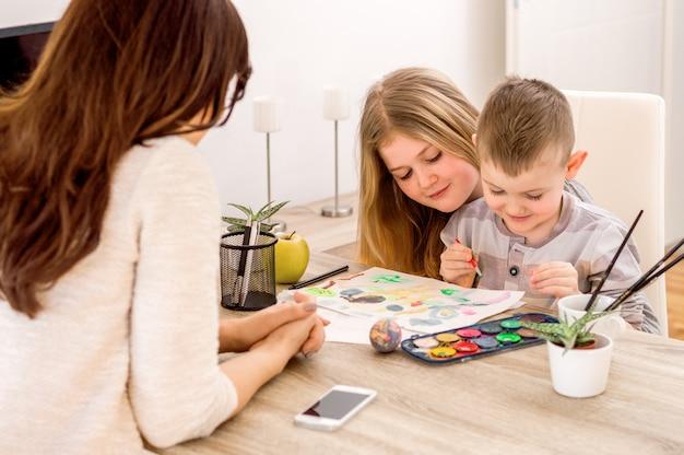 Kinderen met moeder schilderen op papier door verf en potloden.