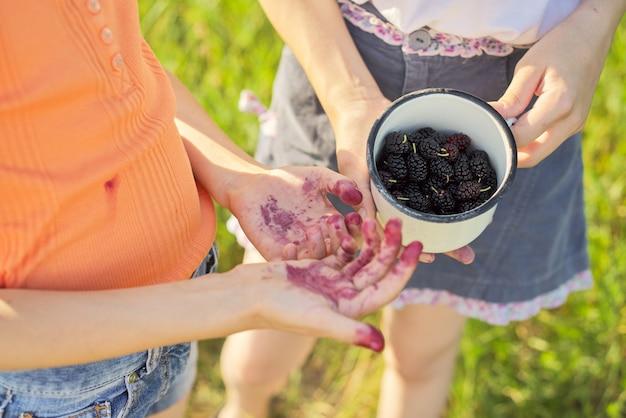 Kinderen met oogst van bessen in mok, moerbeiboom in de zomertuin