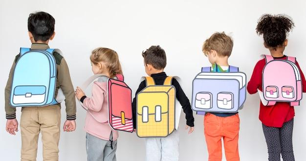 Kinderen met papieren schooltassen