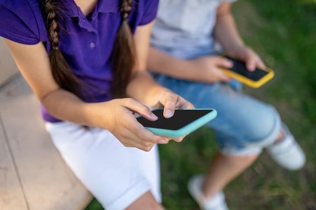 Kinderen met smartphones buiten in de zomer