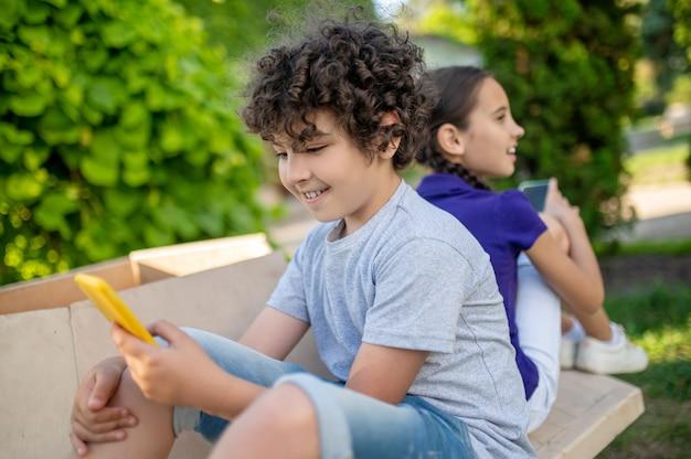 Kinderen met smartphones in groen park