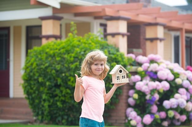 Kinderen met speelgoedhuis. huis in kinderen hand tegen nieuw huis. vastgoedconcept. hypotheek, huisverzekering, toekomstplannen, kinderen beschermen.