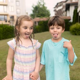 Kinderen met tong uit terwijl hand in hand