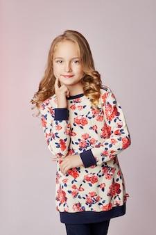 Kinderen mode jonge modellen kinderen poseren. roodharige meisje glimlacht